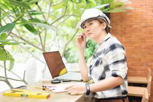 female architect wearing hardhat working on computer
