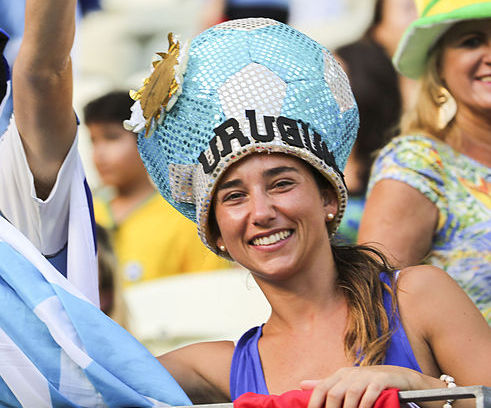 A women dressed in a blue and white soccer-ball hat that reads Uruguay.