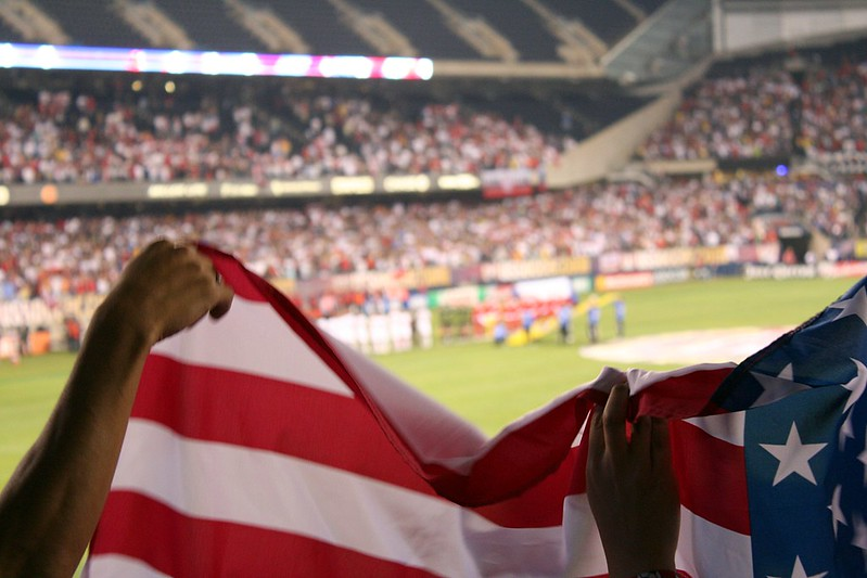 Hands holding a U.S. flag at a soccer game
